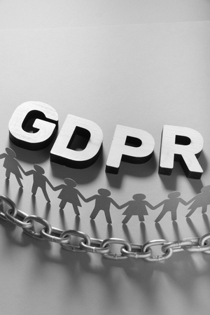 GDPR letters in front of human paper figures and metal chain. General data protection concept.