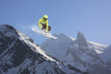 Flying skier on snowy mountains. Extreme sport, alpine ski.