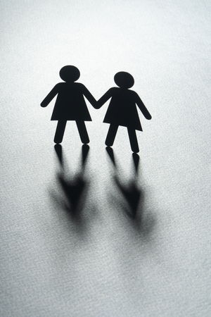 Black paper figure of a female couple holding hands on gray surface. Same-sex marriage, diversity, minorities concept.