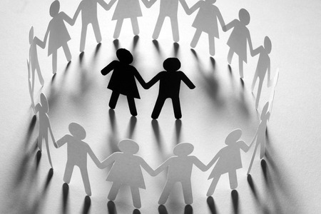Paper figure of a couple surrounded by circle of paper people holding hands on white surface. Bulling, minorities, conflict concept.