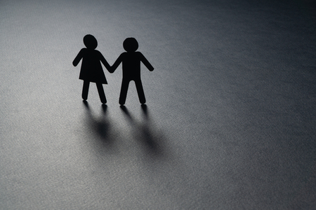 Black paper figure of a couple holding hands on gray surface. Loneliness, childless, old age concept.