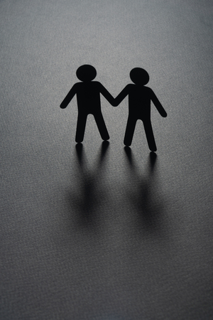 Black paper figure of a male couple holding hands on gray surface. Same-sex marriage, diversity, minorities concept. 写真素材
