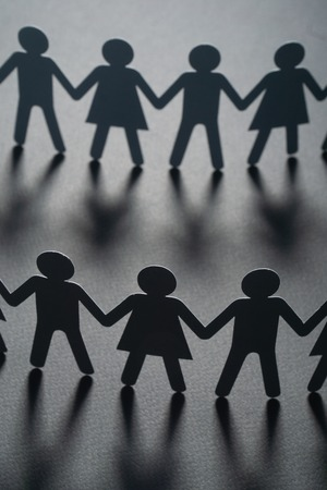 Paper people holding hands on gray surface. Community, union concept. Society and support. Stock Photo