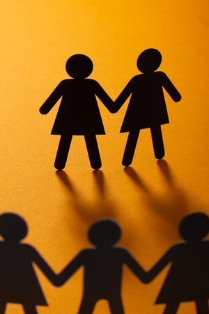 Black paper figure of a female couple in front of a crowd of paper people holding hands on vivid orange background. Social movement, minorities, same-sex marriage concept.
