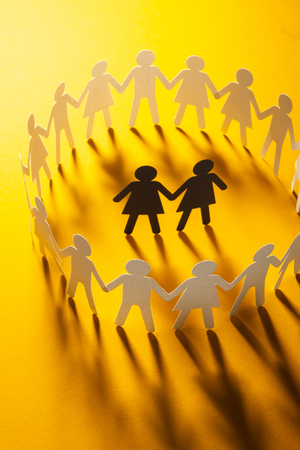 Paper figure of female couple surrounded by circle of paper people holding hands on yellow surface. Bulling, minorities, conflict concept.