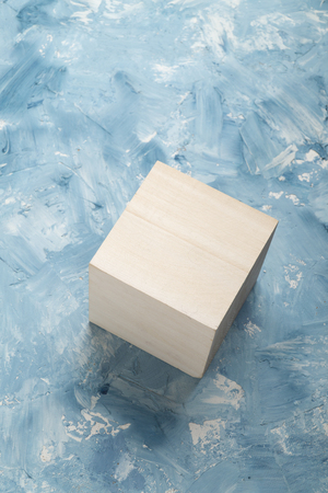 Bright wood cube on white and blue painting surface. Wooden cube and a piece of fine art studio shot.