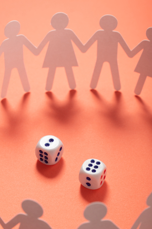 Circle of paper people holding hands in front of two dices. Gambling, addiction concept.