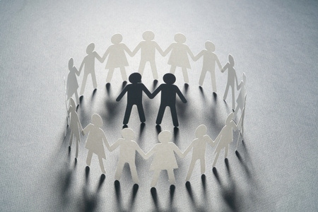 Paper figure of a male couple surrounded by circle of paper people holding hands on white surface. Bulling, minorities, conflict concept.