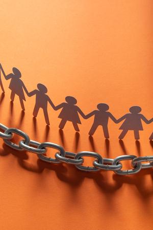 Menschliche Papierfiguren vor Metallkette auf roter Fläche. Freiheit, Menschenrechte, Unabhängigkeit. Standard-Bild