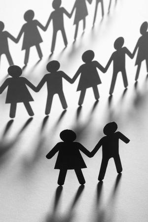Schwarze Papierfigur eines Paares vor einer Menge Papierleute, die Händchen auf weißer Oberfläche halten. Soziale Bewegung, Führung, Protestkonzept.