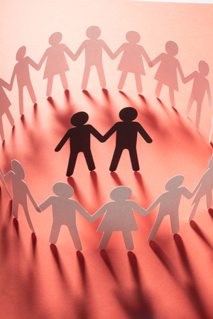 Paper figure of male couple surrounded by circle of paper people holding hands on white surface. Bulling, minorities, conflict concept.