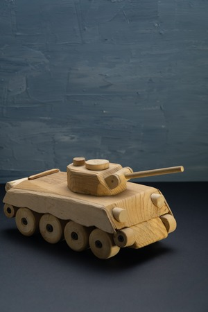 Wood tank on blue painted background. Wooden toy tank studio shot.