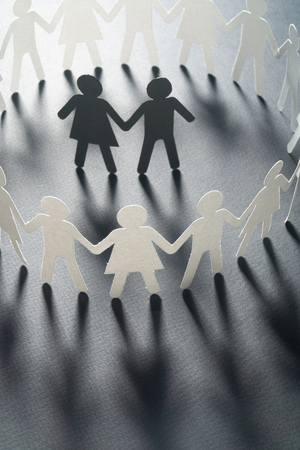 Paper figure of a couple surrounded by circle of paper people holding hands on white surface. Bulling, minorities, conflict concept. Standard-Bild
