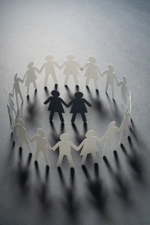 Paper figure of female couple surrounded by circle of paper people holding hands on gray surface. Bulling, minorities, conflict concept. 写真素材