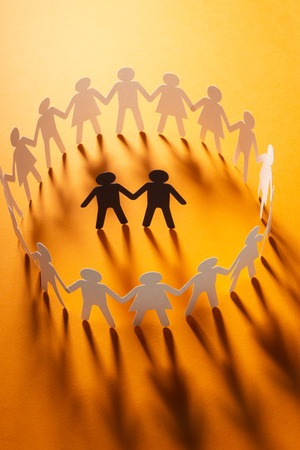 Paper figure of male couple surrounded by circle of paper people holding hands on orange surface. Bulling, minorities, conflict concept.