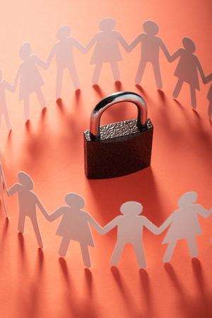 Figures de papier humain debout autour d'un cadenas sur une surface rouge. Liberté, droits de l'homme, indépendance. Banque d'images