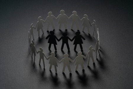 Three human paper figures surrounded by circle of paper people holding hands on dark surface. Bulling, segregation, conflict concept.
