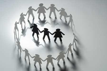Three human paper figures surrounded by circle of paper people holding hands on white surface. Bulling, segregation, conflict concept.