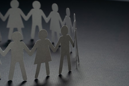 Circle of paper people holding hands on dark surface. Community, union concept. Society and support. Imagens