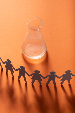 Circle of paper people holding hands in front of empty glass vial. Water scarcity global problem. Addiction, dependency concept.
