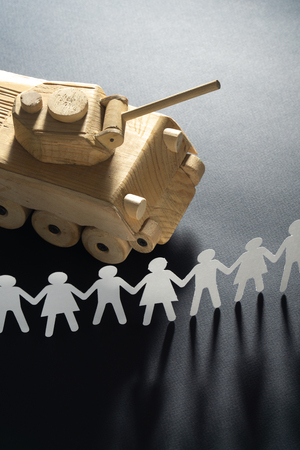 Raw of paper people rallying in front of a tank. Protest, demonstration toy concept. Imagens