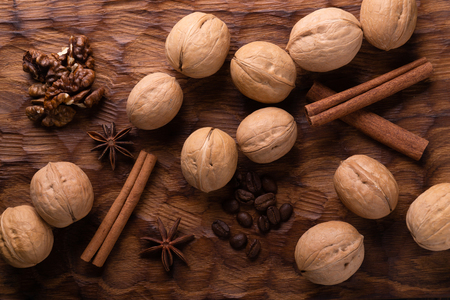 Walnuts, cinnamon, star anise, and coffee beans on wooden cutting board. Nuts and spices on the table. Food composition, top view.