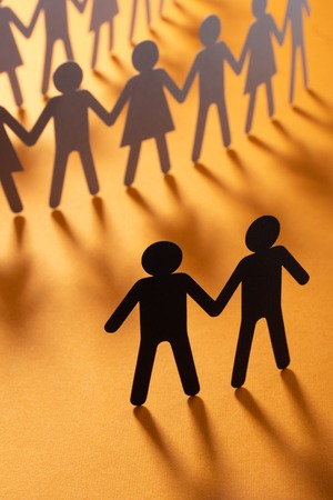 Black paper figure of male couple in front of a crowd of paper people holding hands on orange surface. Social movement, minorities, protest concept. Imagens