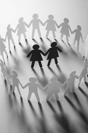 Paper figure of female couple surrounded by circle of paper people holding hands on white surface. Bulling, minorities, conflict concept.