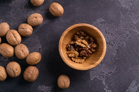 Walnuts in wooden bowl and on blue slate surface. Healthy nuts and seeds composition.
