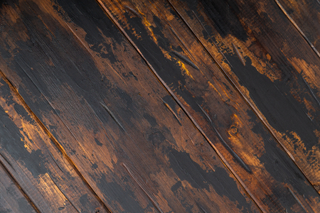 Old wooden surface background, scuffed boards with black paint stains.