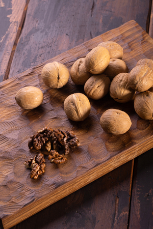 Bunch of walnuts on carved wooden board. Healthy nuts and seeds composition, background.