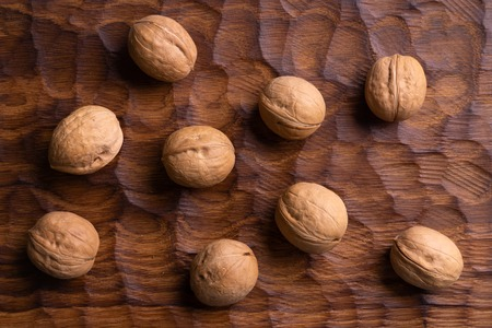 Bunch of whole walnuts lying on carved wooden board. Healthy nuts and seeds composition, background. Imagens
