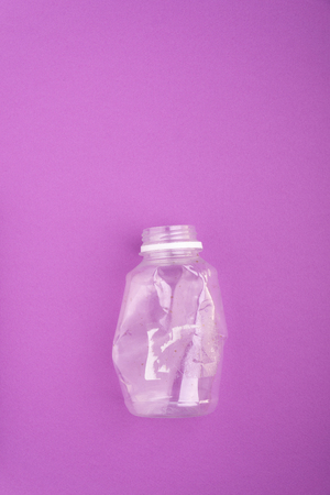 Crashed plastic bottle on blue purple background. Plastic utilisation concept. Ecological problem, global environment. Stock Photo