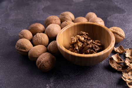 Walnuts in wooden bowl and on black slate surface. Healthy nuts and seeds composition. Stock Photo