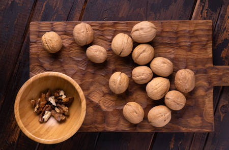 Walnuts in wooden bowl on wooden carved board. Healthy nuts and seeds composition.