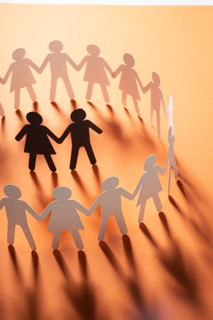 Figura di carta di una coppia circondata da un cerchio di persone di carta che si tengono per mano sulla superficie rossa. Bulling, minoranze, concetto di conflitto.