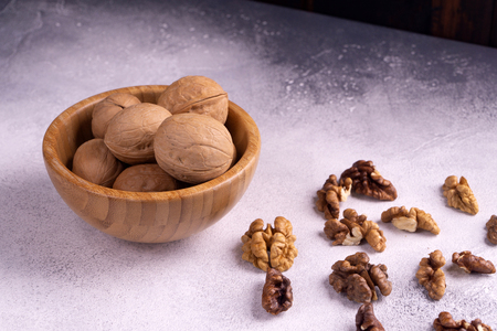 Walnuts in wooden bowl on bright textured surface. Healthy nuts and seeds composition.