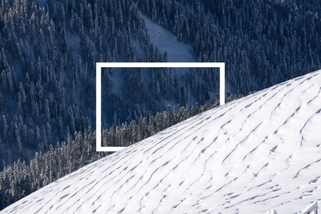 Winter mountain slope and forest with white rectangle frame in the middle, snow surface created by a wind on foreground. Nature mountain landscape backound. 免版税图像