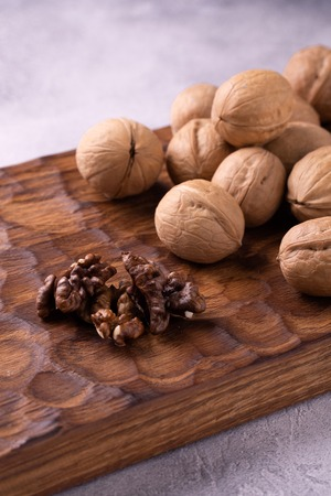 Bunch of whole walnuts on carved wooden board. Healthy nuts and seeds composition, background. Imagens