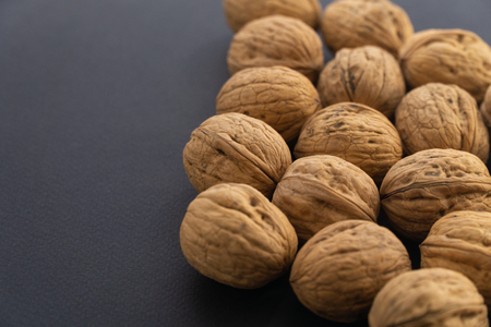 Walnuts in shell on black surface, side view. Healthy nuts and seeds background.