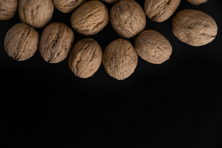 Walnuts in the shell on black surface, top view. Background of round walnuts. Healthy nuts and seeds composition.