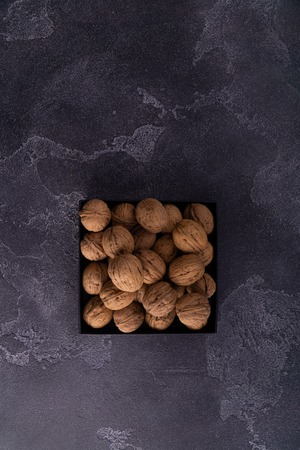 Whole and cracked walnuts on a square plate on blue textured surface, top view. Healthy nuts and seeds composition.