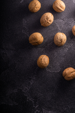 Bunch of whole walnuts on dark blue slate background. Healthy diet composition. Imagens