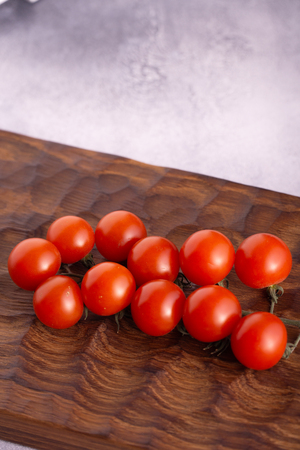Fresh tomatoes on carved wooden cutting board and bright textured surface.