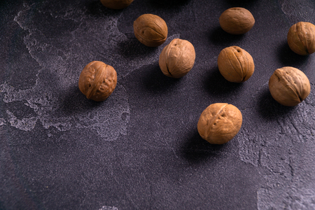 Bunch of whole walnuts on dark blue slate background. Healthy diet composition.