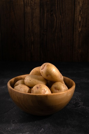 Heap of fresh clean potatoes in a wooden bowl on dark textured surface. Organic food, carbs, tubers.