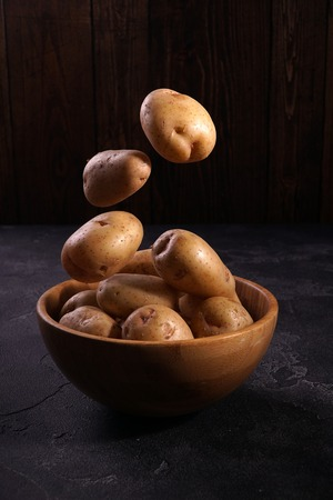 Fresh clean potatoes soaring above the wooden bowl on wooden textured background. Organic food, carbs, tubers. 스톡 콘텐츠