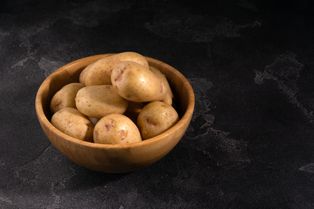 Heap of fresh potatoes in a wooden bowl on dark textured surface. Organic food, carbs, tubers. Banco de Imagens