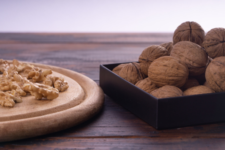 Cracked and whole walnuts on round wooden plate and wooden table, side view. Healthy nuts and seeds composition.