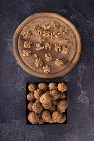 Whole and cracked walnuts on square and round plates on blue textured surface, top view. Healthy nuts and seeds composition.